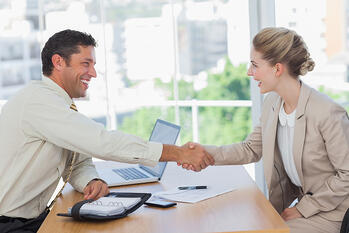 Blonde woman shaking hands while having an interview in office
