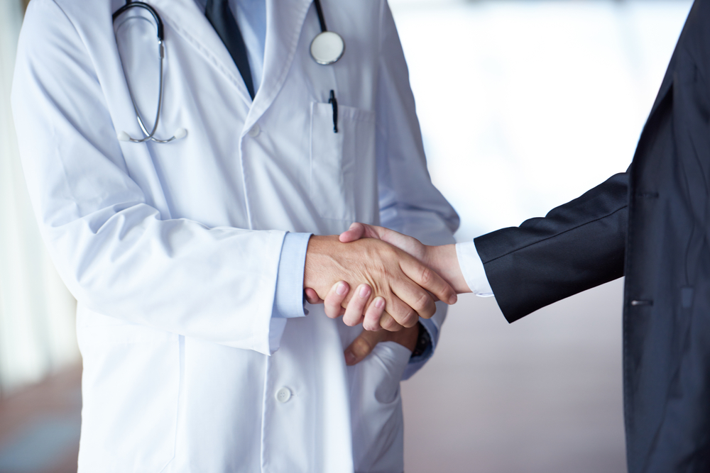 doctor handshake with a patient at doctors bright modern office in hospital-5